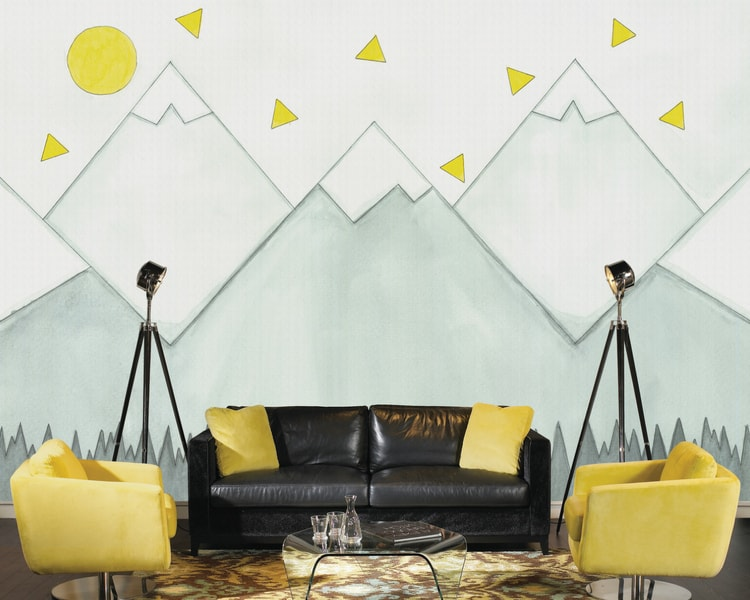 Mountain Mural Wallpaper, as seen in this living room, is a painting of grey mountains under a yellow sun and triangles. Removable wallpaper sold by AboutMurals.ca