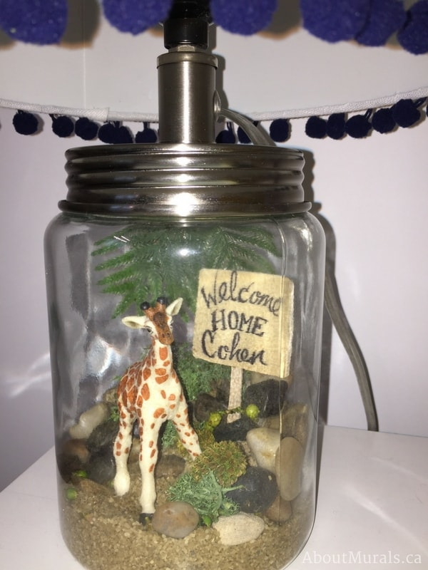"A close up of a personalized lamp with a giraffe, rocks, leaves and sign reading ""Welcome Home Cohen"" created by Sherry Holmes for the Holmes Next Generation TV Show."