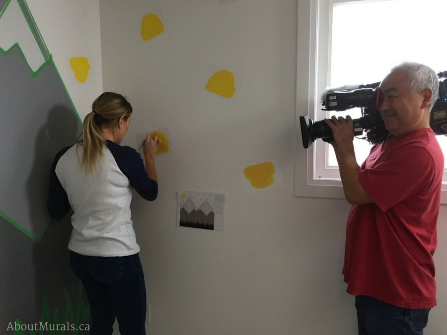 Sherry Holmes learns how to paint yellow triangles and a mountain mural with Adrienne of AboutMurals.ca for the Holmes Next Generation TV show