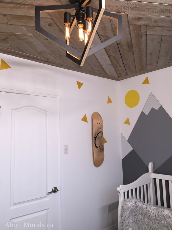 "A mountain mural, painted by Adrienne of AboutMurals.ca, sits beside a rustic, custom skateboard with the initial ""C"" for baby Cohen."