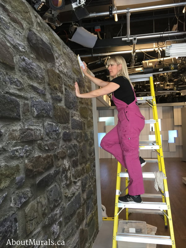 A stone wallpaper on cityline that is being hung by Adrienne of AboutMurals.ca