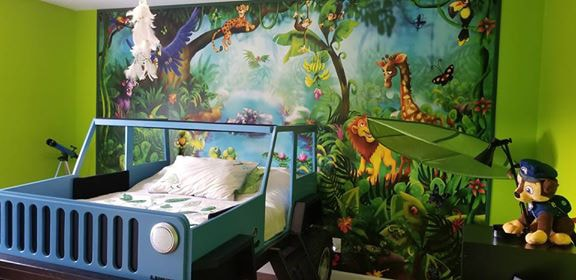 A kids jungle wallpaper sits behind a jeep bed in a boy's room, sold by AboutMurals.ca