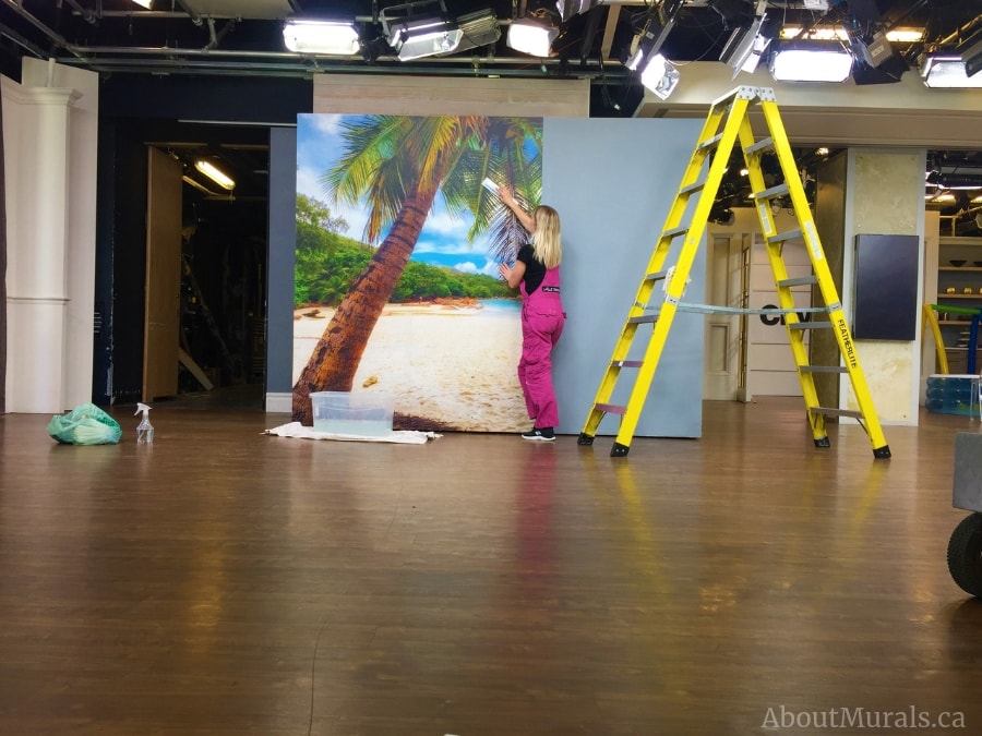 Adrienne of AboutMurals.ca hangs tropical wallpaper on set at Cityline.