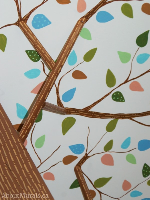 Muralist Adrienne of AboutMurals.ca hand-painted leaves on a ceiling and a wooden structure to look like a tree trunk