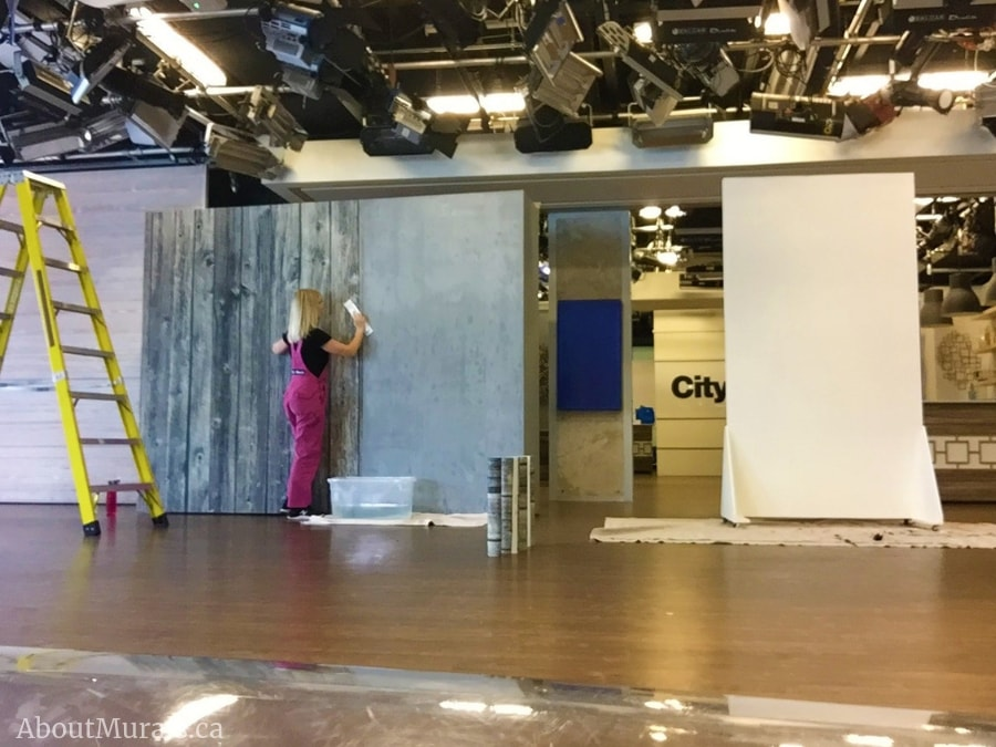 Adrienne hanging a wood look wallpaper on set at Cityline